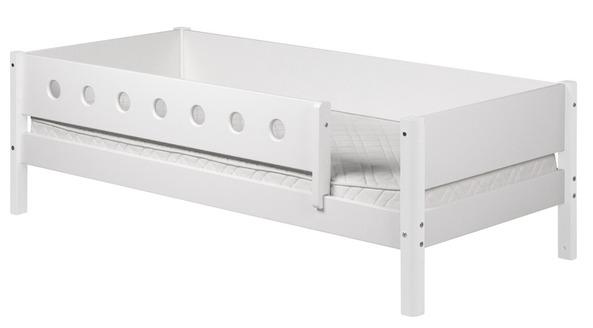 Białe łóżko dziecięce z poręczami zabezpieczającymi